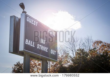 Close up of a scoreboard at a fenced in little league baseball field in the afternoon, with artificial sun flare added.