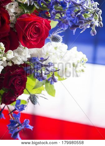 Red, white, and blue flowers from a ceremonial wreath in honor and remembrance.