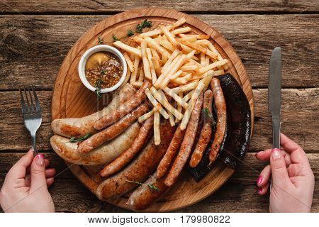 Fat junk food. Unrecognizable person having grilled sausages with sauce and french fries, top view. German cuisine, traditional beer snack