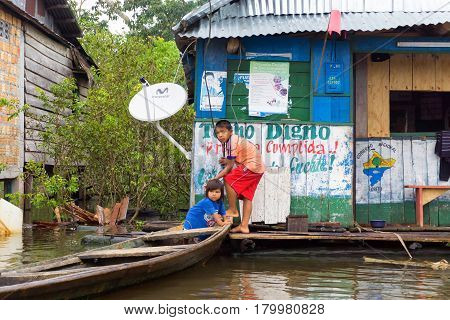 IQUITOS PERU - MARCH 17: Children with a canoe on the river in Iquitos Peru on March 17 2015