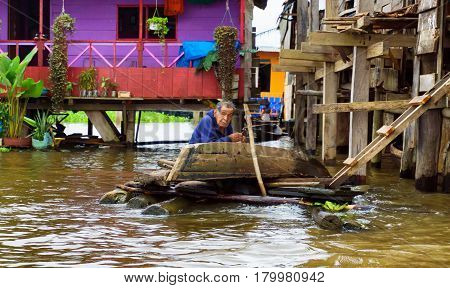 IQUITOS PERU - MARCH 17: Elderly man fixes a canoe in Iquitos Peru on March 17 2015