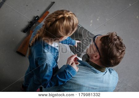 Good shot. Top view of a girl pointing at the target while being with her father in the shooting gallery