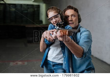 First shooting lesson. Cheerful positive pretty girl wearing protective glasses and trying to shoot while being helped by her father