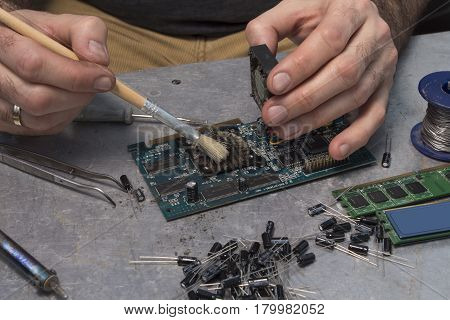 Overheating graphics card. The man's hands remove the dust from the integrated circuit.Fan brush cleaning on integrated circuit.
