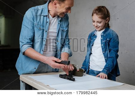 Positive mood. Delighted cheerful nice father pointing at the disassembled handgun and looking at his daughter while smiling
