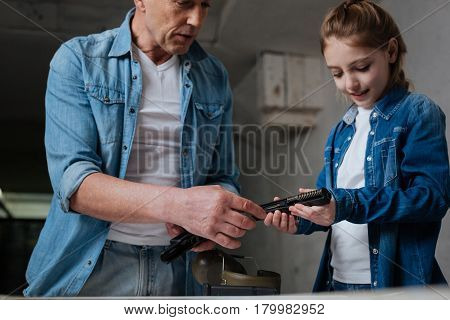Learning about weapon. Pleasant cute nice girl holding a handgun and looking at its details while having a lesson on weapons