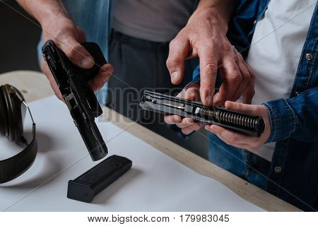 Handgun construction. Nice pleasant handsome man standing near his daughter and pointing at the handgun spring while showing her the construction of a gun