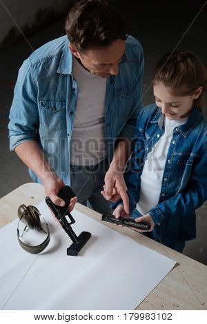 What is inside. Nice pleasant intelligent man showing his daughter a gun and pointing at its details while teaching her about weapon