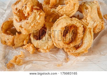 Closeup view of delicious fresh fried calamari rings on white paper. Seafood, Japanese cuisine, fast food, appetizing snack for beer.