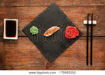 Japanese sushi background, nigiri served on black slate, on wooden rustic table, flat lay. Healthy national seafood, gourmet delicacy.