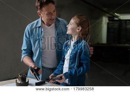 Family relationships. Cheerful positive nice father looking at his daughter and smiling while holding a handgun