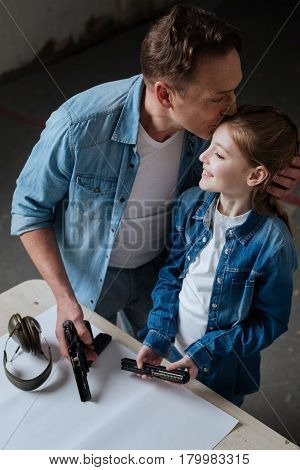I love you. Delighted caring pleasant father holding a gun and kissing his daughter while standing near her