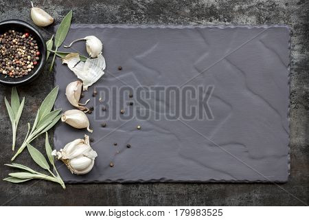 Food background on slate, top view, with garlic cloves, sage leaves and peppercorns.