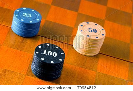 Winning plastic chips for poker lie on a chessboard popular board games around the world poker and chess