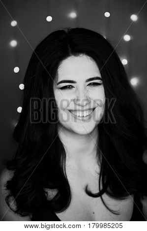 Portrait of a beautiful smiling brunette with long hair. Perky. Studio photography , bokeh light bulbs.Black and white