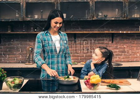 Time to cook together. Photo of mother and little daughter. Woman teaching girl how to cook. Teflon pan full of organic vegetables. Woman using modern electric stove