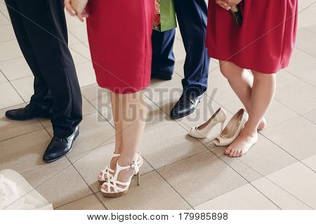 Beautiful bridesmaids and groomsmen standing in church during wedding ceremony tired elegant bridesmaid standing barefoot near stylish high heels feet closeup