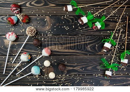 colorful cake pops and chocolate marshmallows set on wooden background for text typing. composition of cake pops, marshmallows, strawberry an chocolate balls on wooden table.