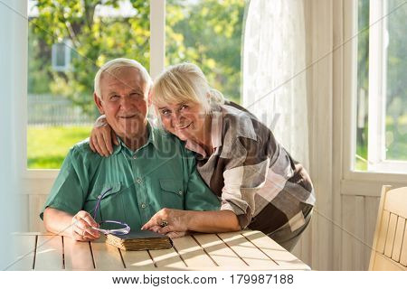 Senior couple with a book. Man and woman smiling indoor. Two lives, one story.