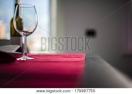 glasses and red wine bottle on a red setting table