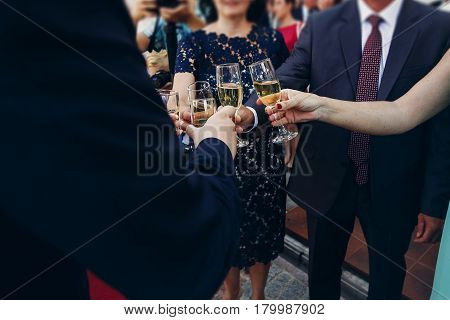 Newlywed Bride And Groom Toasting Champagne With Friends And Family At Wedding Reception In Restaura