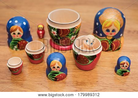 Many open Russian nested dolls on a wooden table with a little doll in one of them