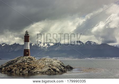 red and white lighthouse on island with fur seals on it near ushuaia , argentina, clouded sky