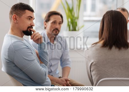 Keep in mind. Profile photo of serious bearded man that sitting in semi position while listening attentively to his opponents during taking part at the conference