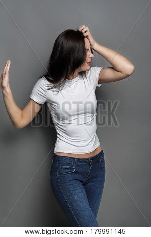 Unpleasant feeling. Woman expressing disgust, grimacing and gesturing to camera on gray studio background