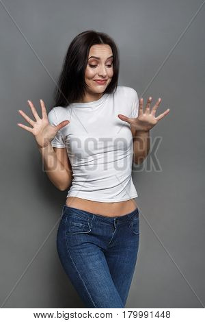 Unpleasant situation. Woman feeling disgust, afraid to be attacked,  gray studio background