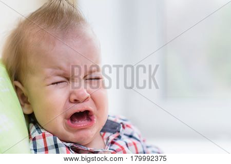 Baby Crying Sitting On A Chair At Home