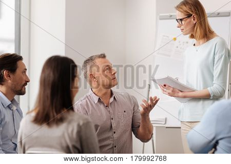 Take an order. Attractive woman listening attentively to her colleague standing in semi position, holding notebook