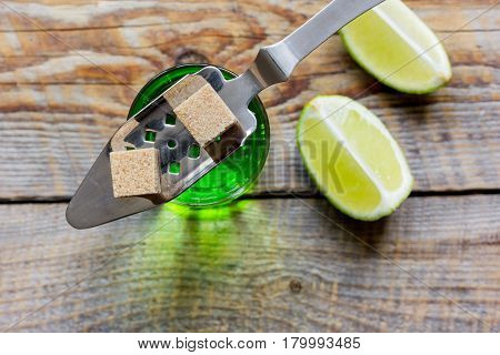absinthe shots with fresh green lime slices and sugar cubes on dark bar table background top view