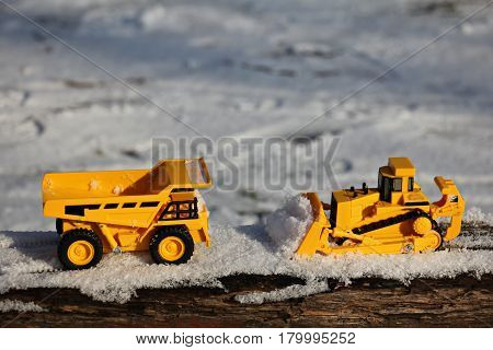 Toy bulldozer and dumper at work in snow .