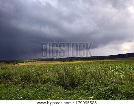 Cloudy sky over the meadows - green grass and dark clouds.