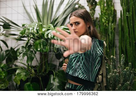 Angry young woman holding pineapple and showing stop gesture