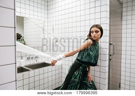 Pretty young woman with hands tied by toilet paper going out of water closet
