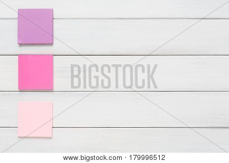 Stationery office and school supply concept - flat lay of colorful sticky notes on white rustic wooden board background, top view with copy space on paper, nobody, objects