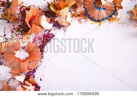 Wooden colorful pencil sharpening shavings, on white isolated background, top view, flat lay, copy space