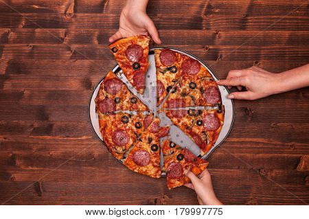 Hands taking pizza slices off the baking pan - top view copy space