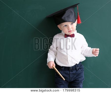 Cute little boy with pointer and magister hat near blackboard