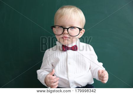 Cute little boy with glasses and blackboard on background
