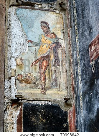 POMPEII, ITALY - MAY 13, 2014: Antique fresco depicting the god Priapus with large phallus. Pompeii is an ancient Roman city died from the eruption of Mount Vesuvius in 79 AD.