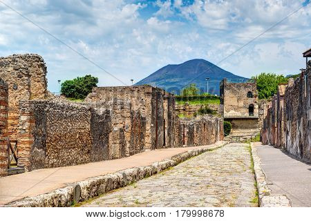 Street in Pompeii overlooking the Vesuvius. Pompeii is an ancient Roman city died from the eruption of Mount Vesuvius in 79 AD. Italy.