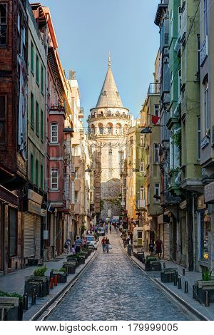 ISTANBUL - MAY 26, 2013: View of old narrow street with the Galata Tower on may 26 2013 in Istanbul, Turkey. The Galata Tower is the greatest monument of Middle Ages.