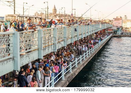 ISTANBUL - MAY 26, 2013: Fishermen and tourists are on the Galata Bridge in Istanbul, Turkey. The Galata Bridge is one of the main attractions of Istanbul.