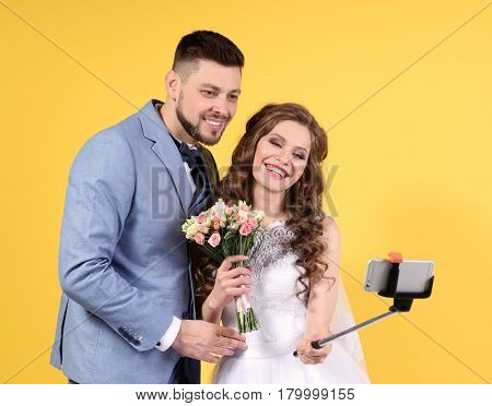 Happy wedding couple making selfie on color background