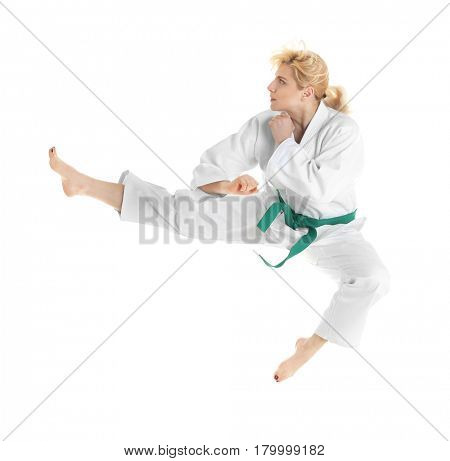 Young sporty woman practicing martial arts on white background