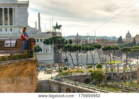 Young female tourist looks at the Forum of Trajan and the Piazza Venezia in Rome, Italy