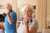Portrait of an active senior couple in sportswear smiling and lifting dumbells while exercising together in their living room at home poster